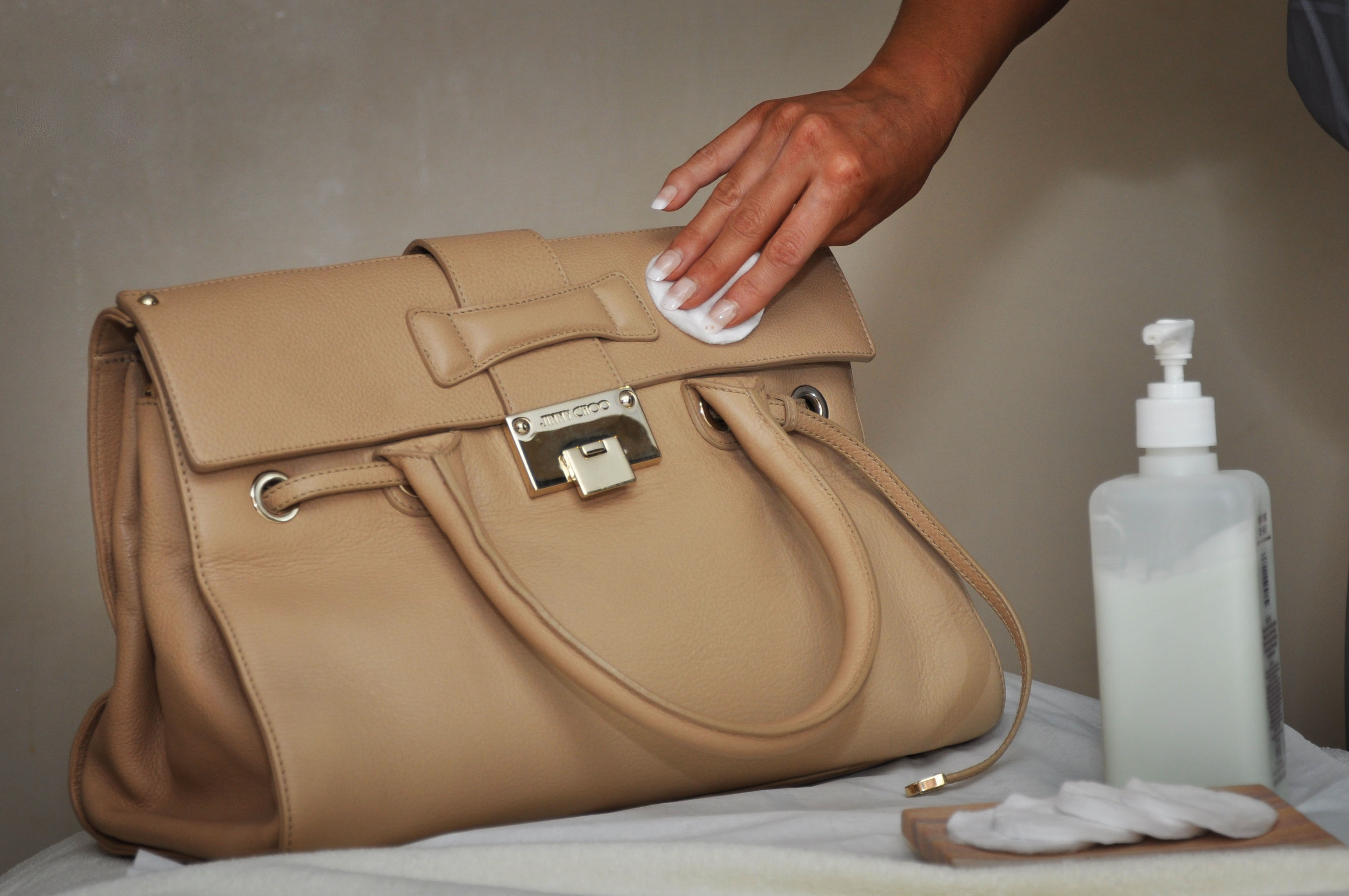 use nail polish remover to clean art leather purse