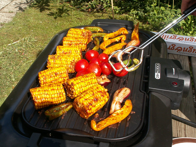 tomatoes and corn grilling on electric barbecue