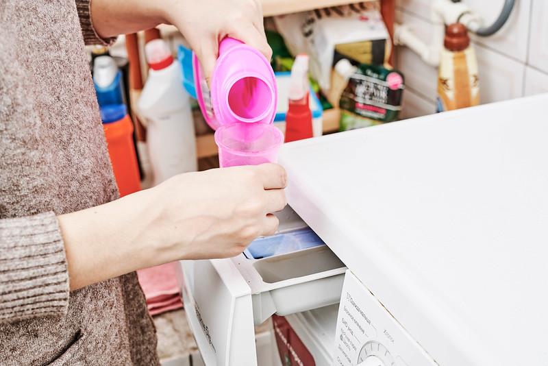 woman putting liquid detergent in washer